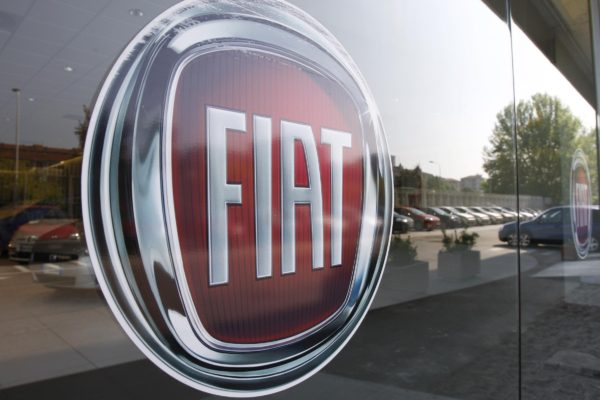 FILE - In this May 7, 2009 file photo, a Fiat logo is seen on a car retailer's window in Milan, Italy. Fiat CEO Sergio Marchionne's corporate jet has served a sort of mile-high headquarters as the CEO crisscrosses oceans and continents to integrate and expand Fiat and Chrysler. The process of choosing a headquarters for what would be the world's seventh largest automaker -- based on combined 2010 sales of 3.74 million vehicle -- is as politically fraught as any Olympic city bid.  Marchionne, who will remain the CEO of Fiat, will be chief operational officer for North America, including Chrysler. (AP Photo/Luca Bruno, File)