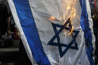 Demonstrators burn an Israeli national flag during an anti-Israel protest, in front of the Israeli embassy, in Bangkok July 25, 2014. Gazan authorities said Israeli forces shelled a shelter at a U.N.-run school on Thursday, killing at least 15 people as the Palestinian death toll in the conflict climbed over 760 and attempts at a truce remained elusive. The Israeli military said it was investigating the incident. REUTERS/Athit Perawongmetha (THAILAND - Tags: POLITICS CIVIL UNREST SOCIETY)